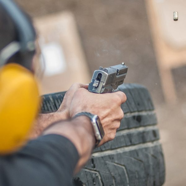 person shooting a target behind a tire